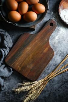 空白の木製のまな板と卵と暗い背景に乾燥小麦