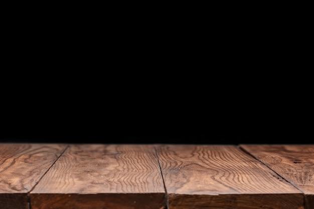 Пустой деревянный стол на фоне черных обоев для настоящего продукта и других вещей.