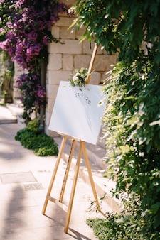 壁と花の茂みの側面図の表面に空白の木製イーゼル