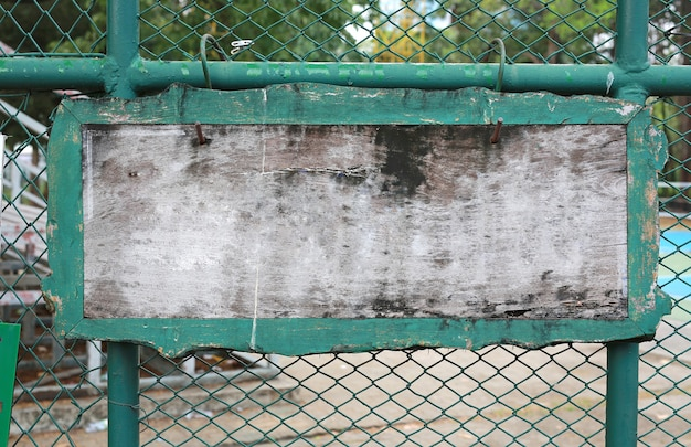 Blank wooden label on steel wire mesh fence.