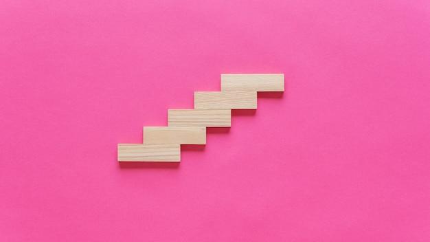 빈 나무 못은 개념적 이미지의 구조처럼 계단에 배치됩니다. 복사 공간이 분홍색 배경 위에.