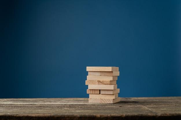 Пустые деревянные колышки сложены на деревенском деревянном столе в концептуальном изображении. на синем фоне.