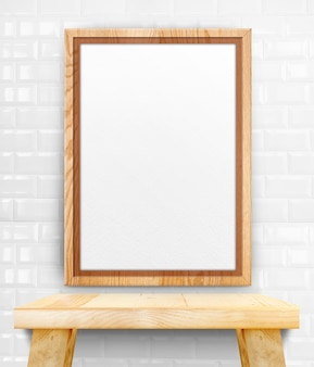 Blank wooden photo frame hanging at white tile wall on wood table.