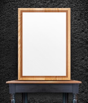 Blank wooden photo frame leaning at black stone wall on vintage wood table