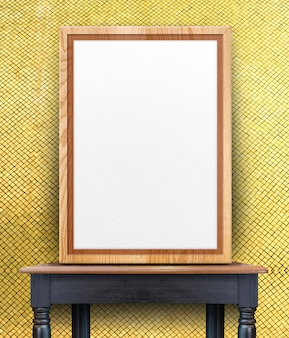 Blank wooden photo frame leaning at gold mosaic tile wall on black vintage wood table