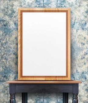Blank wooden photo frame leaning at grunge crack blue concrete wall on black vintage wood