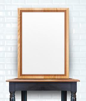 Blank wooden photo frame leaning at white glossy tile wall on vintage wood table