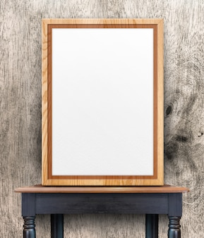Blank wooden photo frame leaning at wood wall on wood table