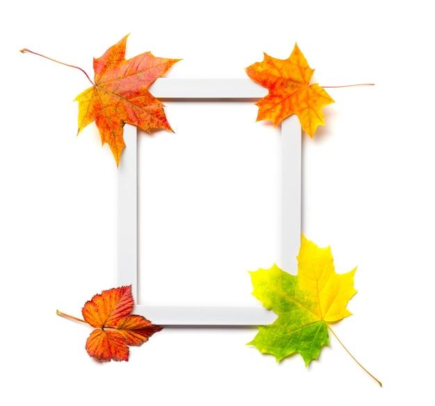 白い背景で隔離のカラフルな紅葉と空白の木製フォトフレーム。秋のモックアップ。