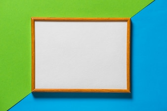 Blank wooden picture frame on blue and green backdrop