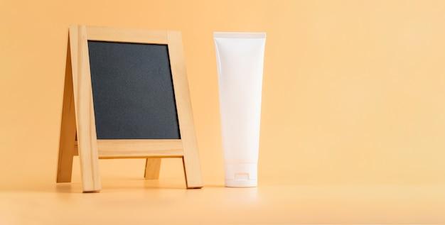オレンジ色の壁に空白の木製看板と白いボトルクリームパッケージ。自然美容製品のコンセプト。