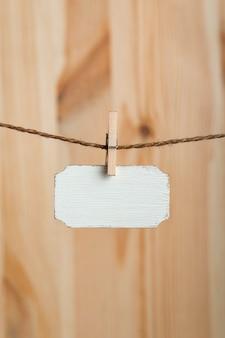 空白の木製看板は、木製の背景のロープに洗濯バサミでぶら下がっています。小さなネームプレート。スペースをコピーします。あなたのテキストのための場所。