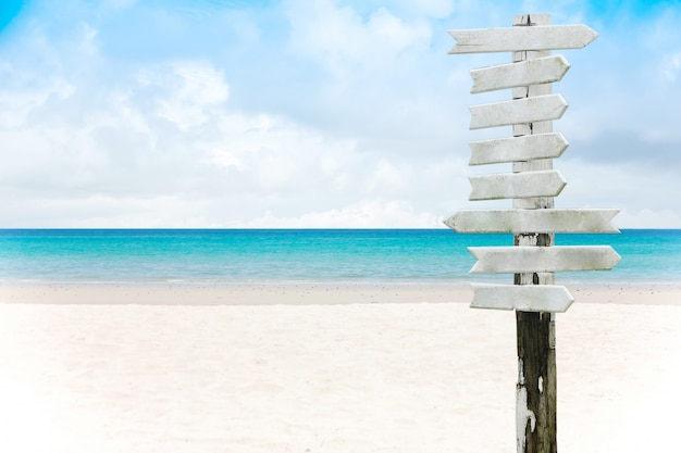 Blank wooden sign on a sand beach and beautiful sea background in summer.