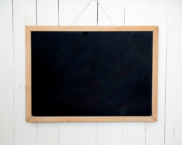 Blank wooden slate hanging on white wall