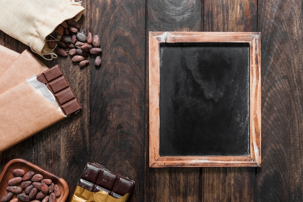 Blank wooden slate with cocoa beans and chocolate bars on wooden table