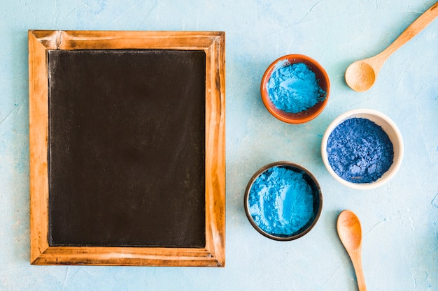 Blank wooden slate with holi colored bowls and wooden spoon on colored background