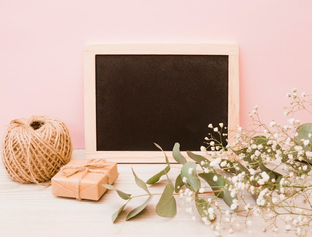 Blank wooden slate with spool; gift box and baby's-breath flowers on wooden desk against pink background