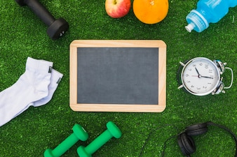 Blank wooden slate with sport equipments and healthy fruits on green turf