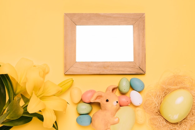 Blank wooden white frame with easter eggs; bunny nest and lily flower on yellow background