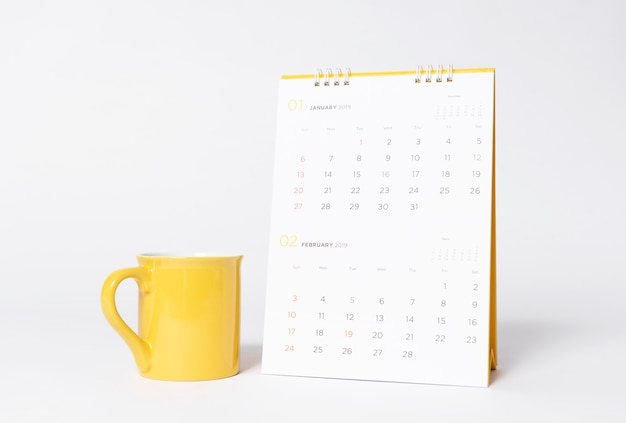 Blank yellow cap mockup and paper spiral calendar year 2019 on gray background.