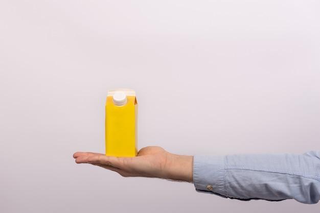 メンズ手のひらにキャップ付きの空白の黄色の段ボール袋。ジュースまたはミルクのパケット。モックアップ。