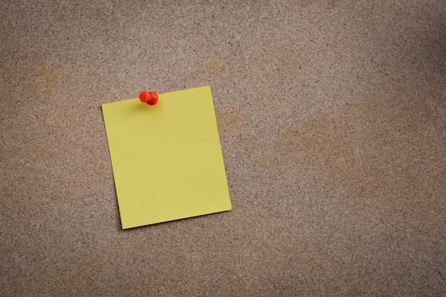 Blank yellow paper note pinned on cork board with white thumbtacks, copy space available