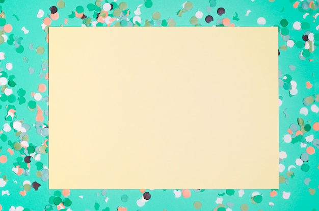 Blank yellow paper with colorful confetti over green background