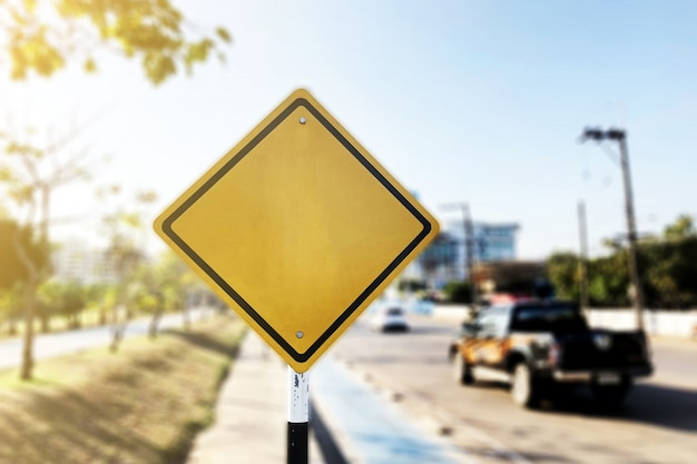 Blank yellow road sign or empty traffic signs on blur street