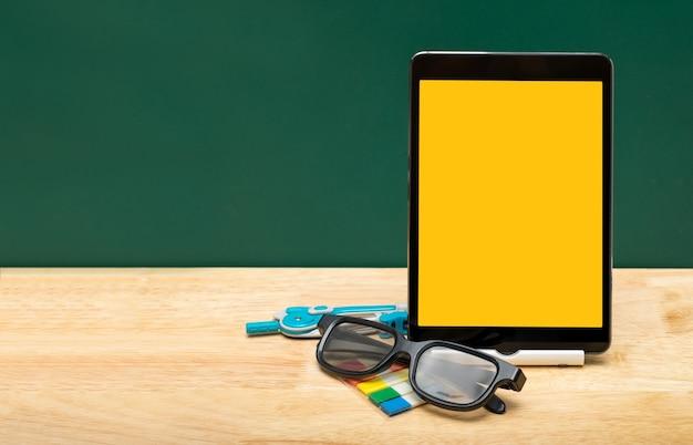 眼鏡を持つ空白の黄色の画面のタブレット