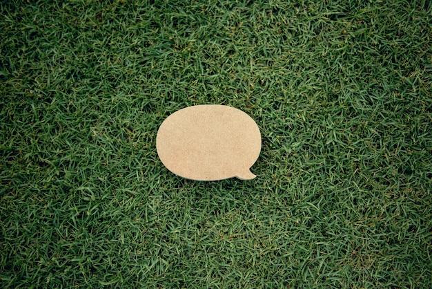 Blank yellow speech bubble pin on green grass background