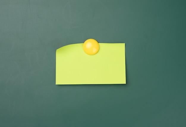 둥근 자석으로 부착된 녹색 분필 보드의 빈 노란색 스티커, 비문 위치