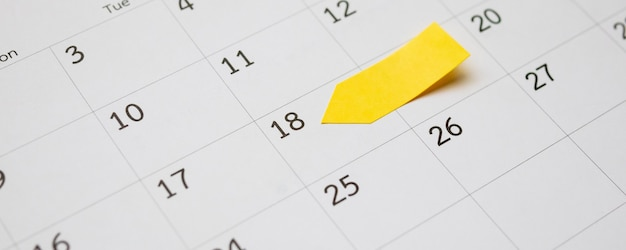 Blank yellow sticky adhesive post on calendar
