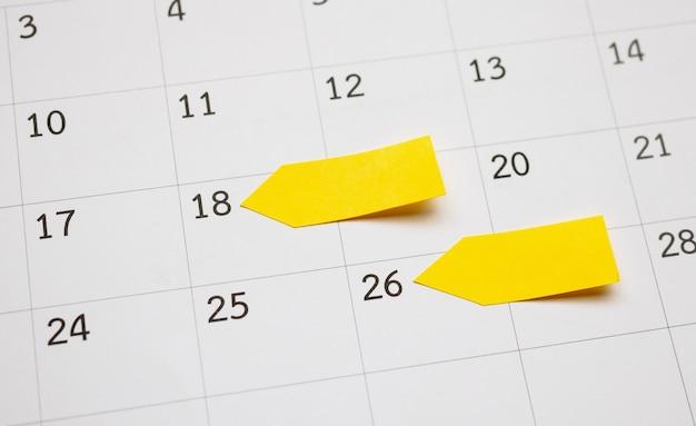 사업 계획 약속 회의 개념에 대 한 달력 페이지 벽에 공간을 가진 빈 노란색 스티커 접착 포스트잇 메모 용지 플래너