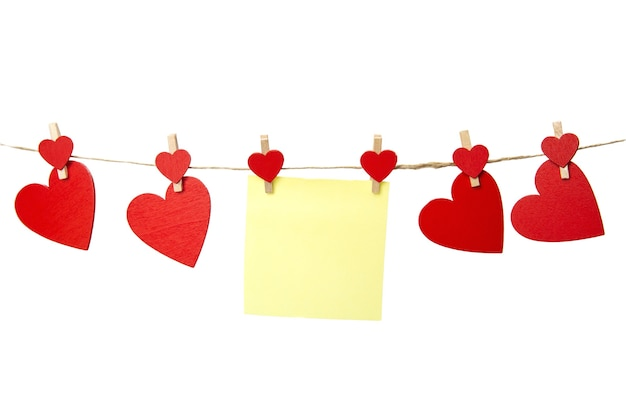 Пустая желтая записка висит при красные сердца, изолированные на белом фоне, романтическая концепция дня святого валентина, копией пространства. место для текста