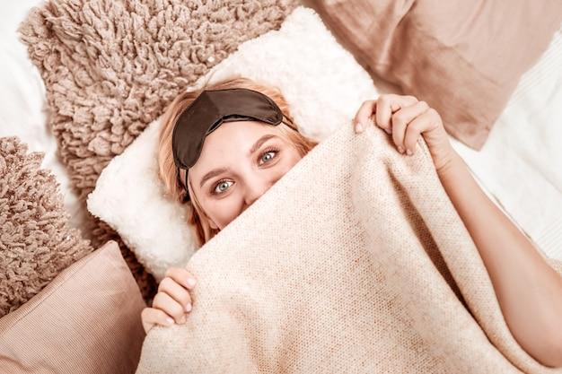 全体に毛布。ふわふわの枕の上に横たわっている間、ふざけて顔を覆っている青い目をした魅力的な明るい髪の女性