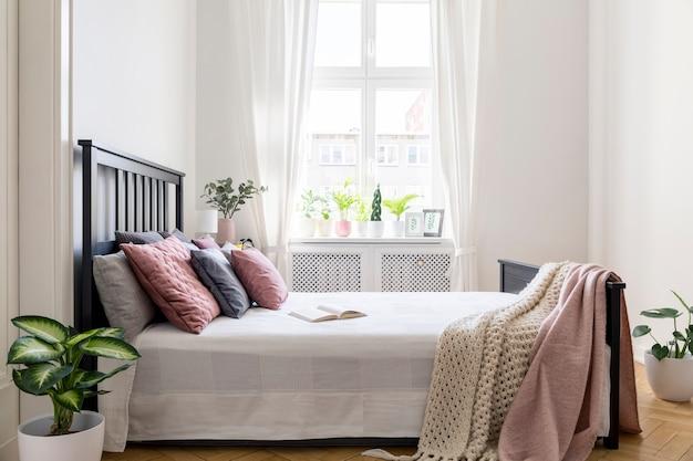 창문이 있는 흰색 침실 내부에 헤드보드가 있는 침대에 담요와 파스텔 쿠션. 실제 사진