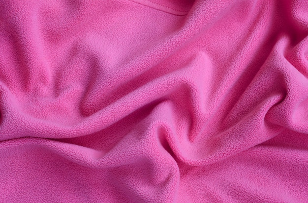 The blanket of furry pink fleece fabric. a background of light pink soft plush fleece material