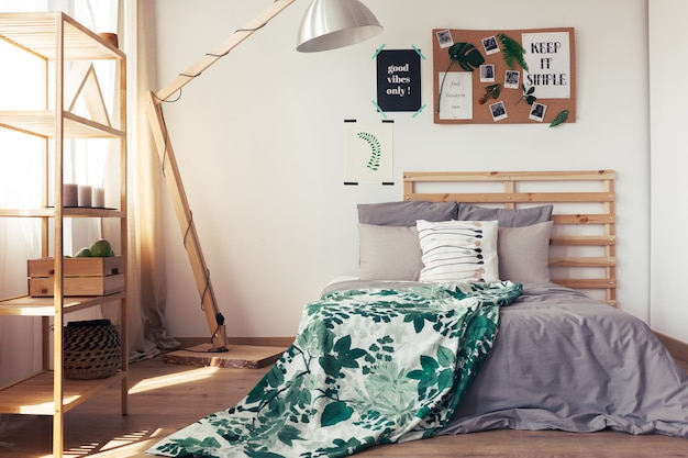 Blanket with nature motif on king-size bed with grey pillows and coverlet in simple bedroom