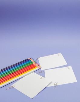 Бланки листов бумаги и цветных карандашей на фиолетовом фоне для проектов и объявлений, копия места