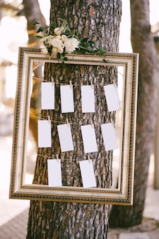 Blanks for the wedding guest list hang in a beautiful frame on a tree seating plan