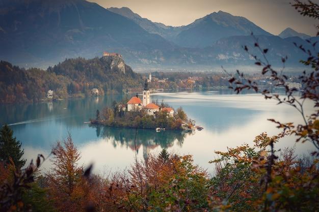 Бледное озеро с островными отражениями в обрамлении осенних цветов деревьев