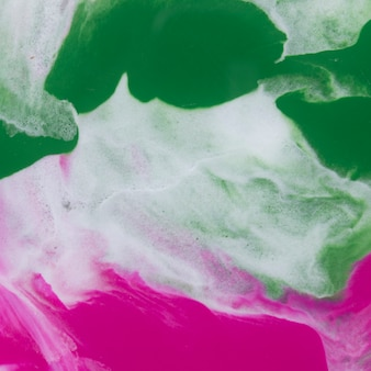 Blend of abstract green and pink watercolor textured on white paper