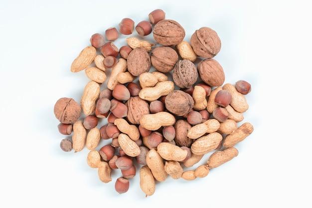白い背景にナッツをブレンドします。ダイエットと健康的な栄養の概念。