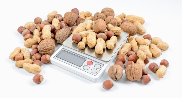 Смесь орехов на электронных весах с белым фоном. концепция диеты и потери веса.