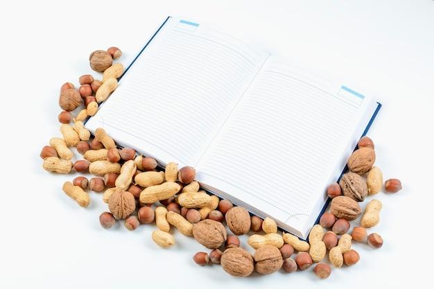 열린 메모장과 흰색 시트와 견과류의 조화. 음식 칼로리 기록 개념