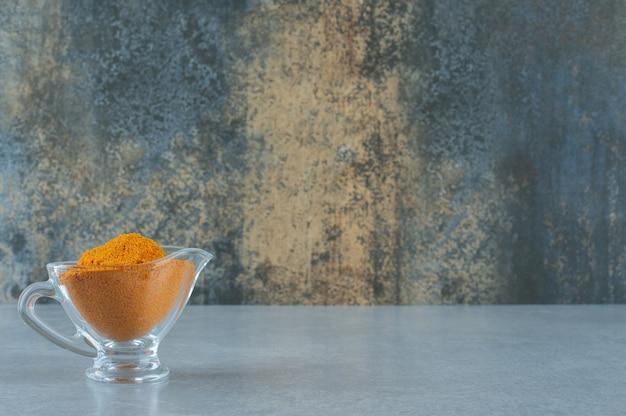 유리 컵에 혼합된 커큐민 분말. 고품질 사진