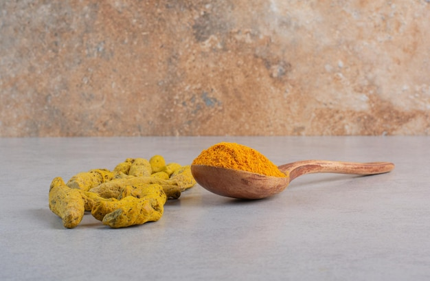Blended curcumin powder in a wooden spoon.
