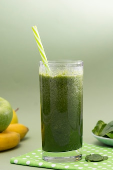 Blended green smoothie glass selective focus, green background. healthy food.