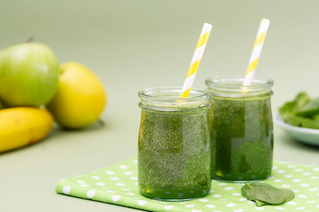 Смешанный фокус зеленого smoothie стеклянный селективный, зеленая предпосылка. здоровая пища.