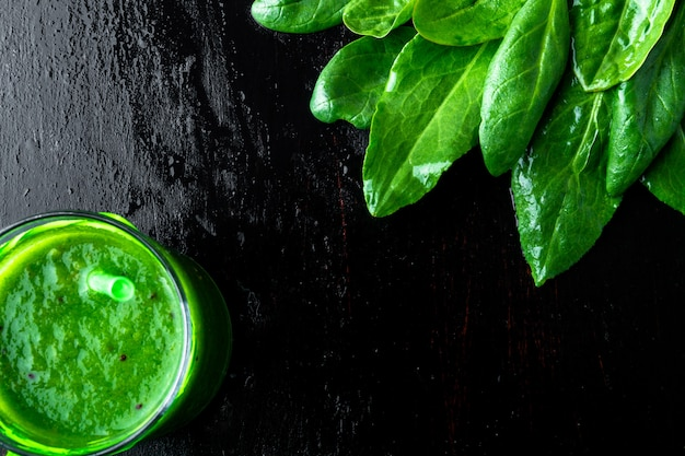 Blended green smoothie with ingredients on black table.